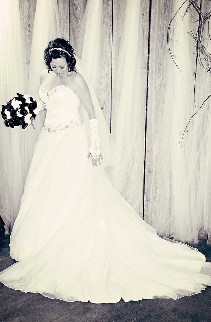 a bride with a bouquet standing in front of a wood plank wall