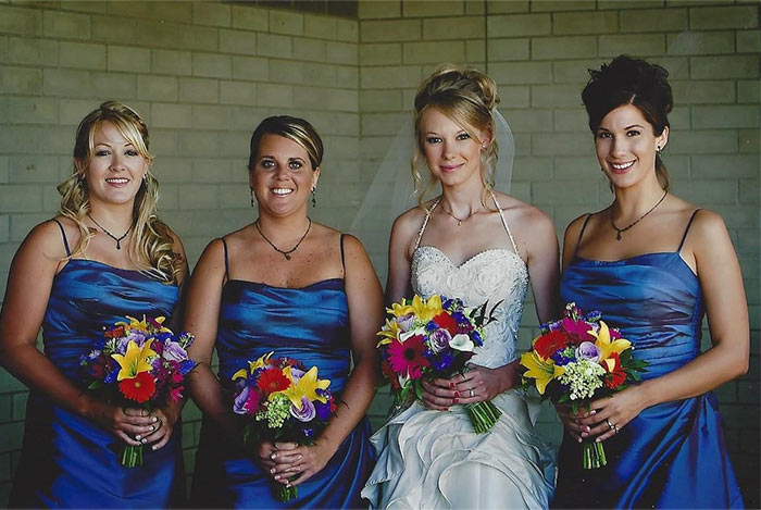 a bride with bridesmaids wearing blue dresses