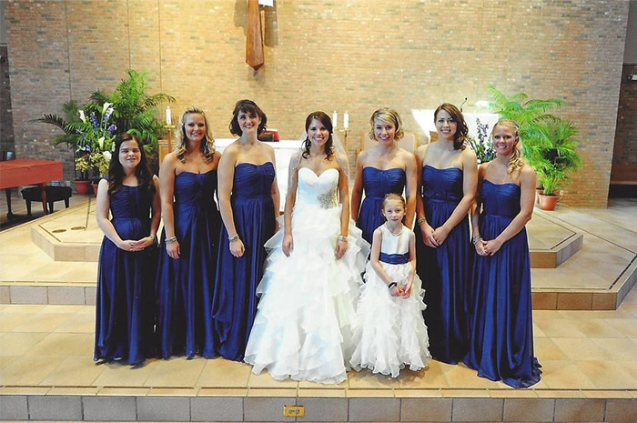 a bride with bridesmaids and flower girl in church