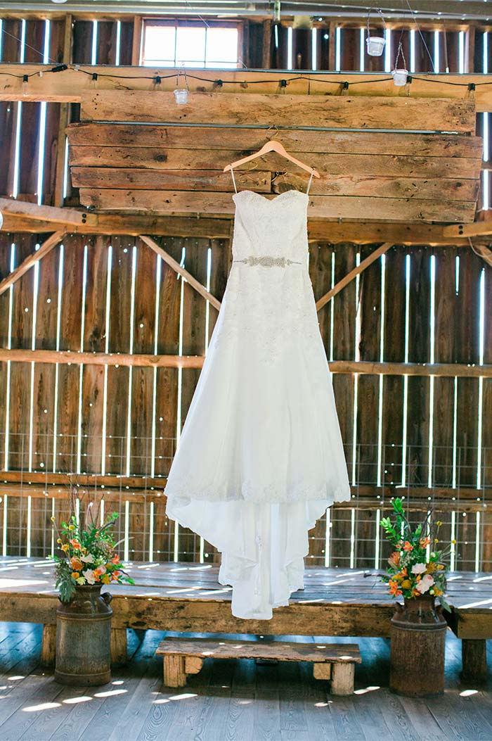 a wedding dress hanging on the outside of a barn