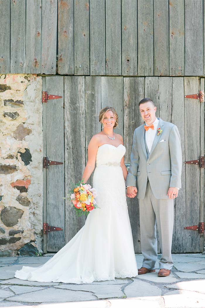 a wedding couple standing outside of a barn