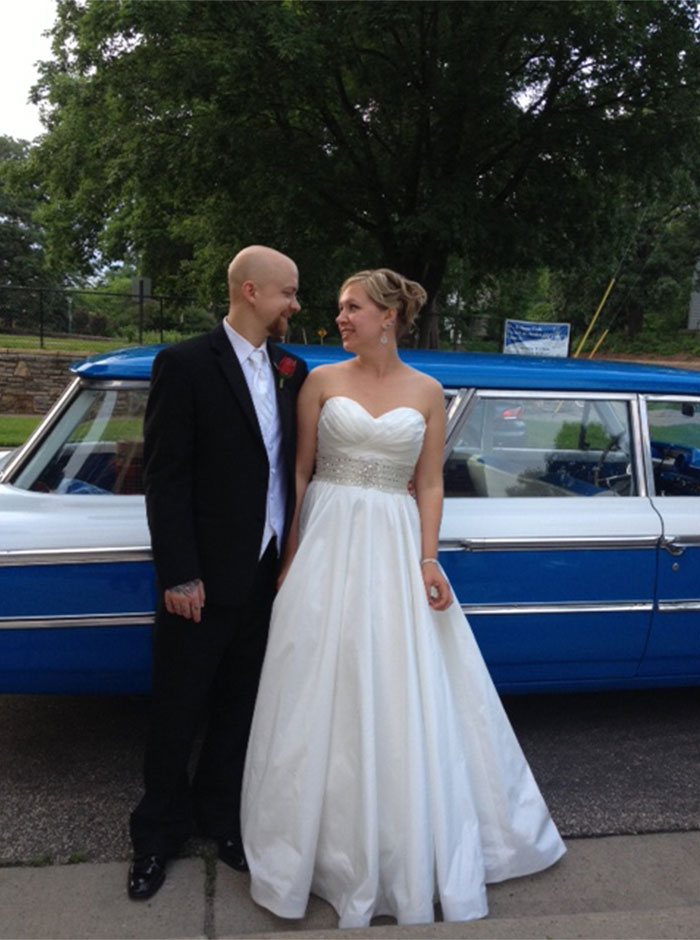 a wedding couple standing in front of a vintage car