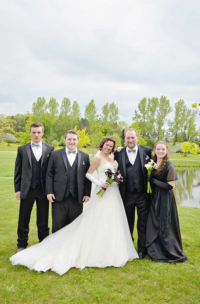 a wedding couple with family near a pond