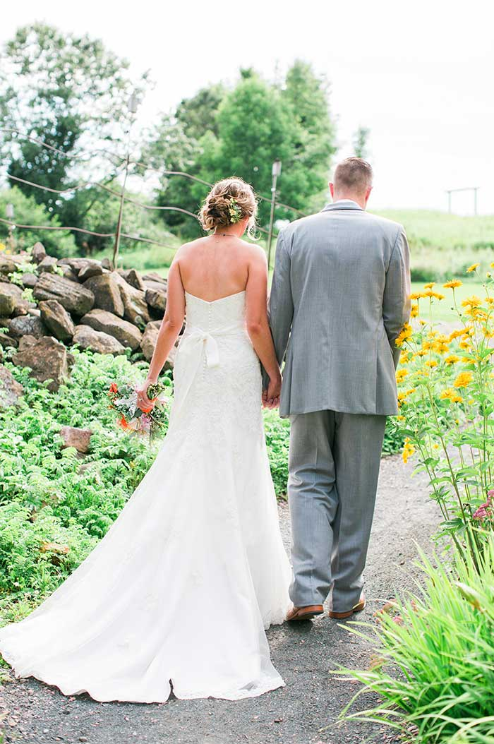a wedding couple walking down a graveled path