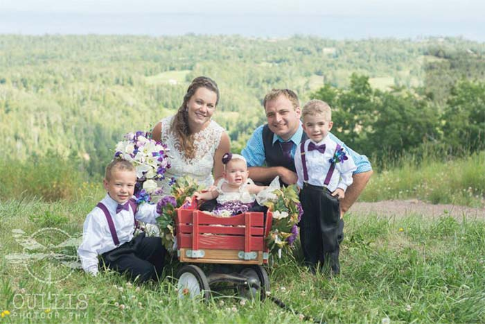 a wedding couple with kids in a wagon