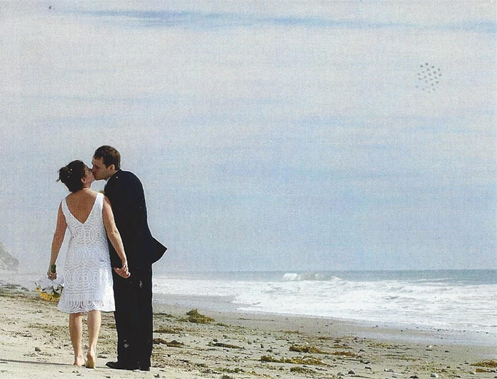 a wedding couple kissing on a beach