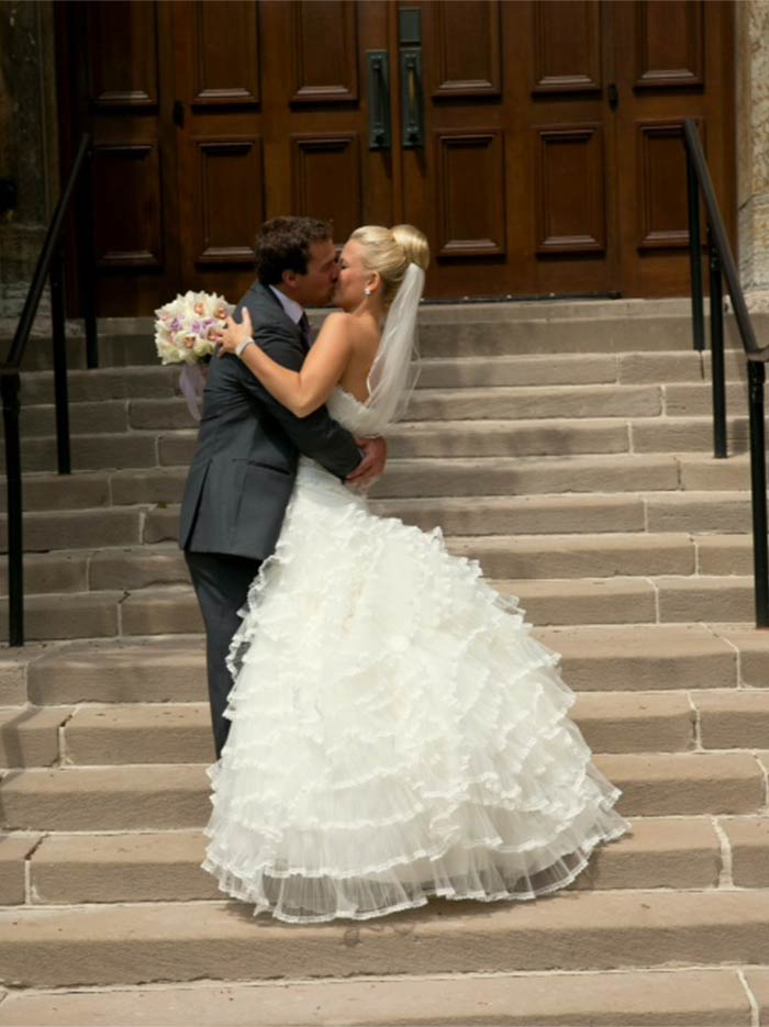 a wedding couple kissing on steps