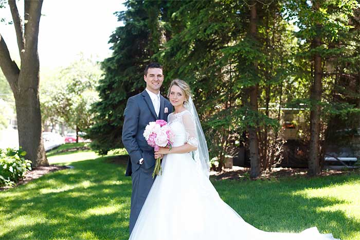 a wedding couple with a pink bouquet
