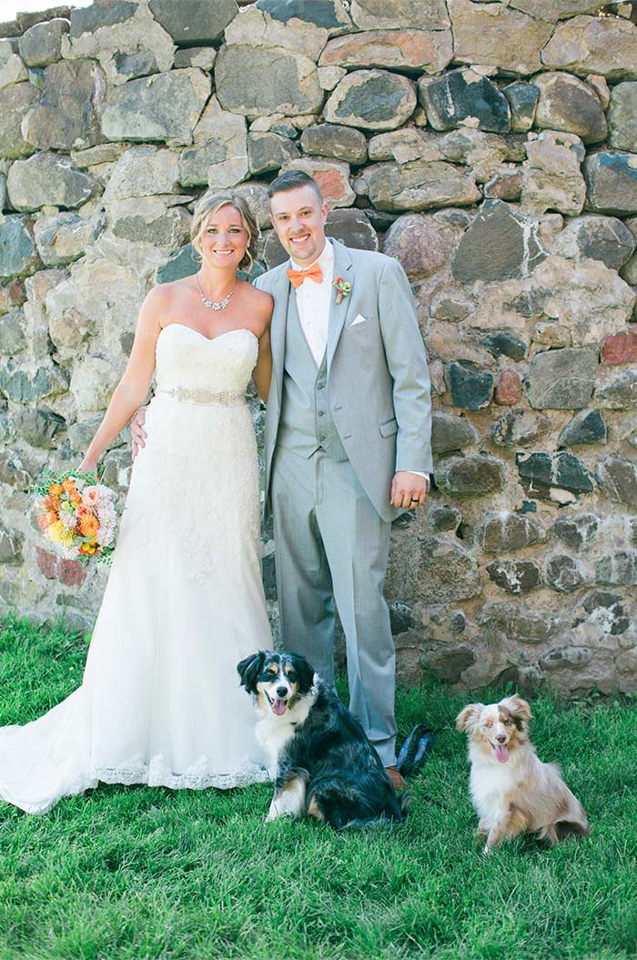 a wedding couple near a stone wall with their dogs