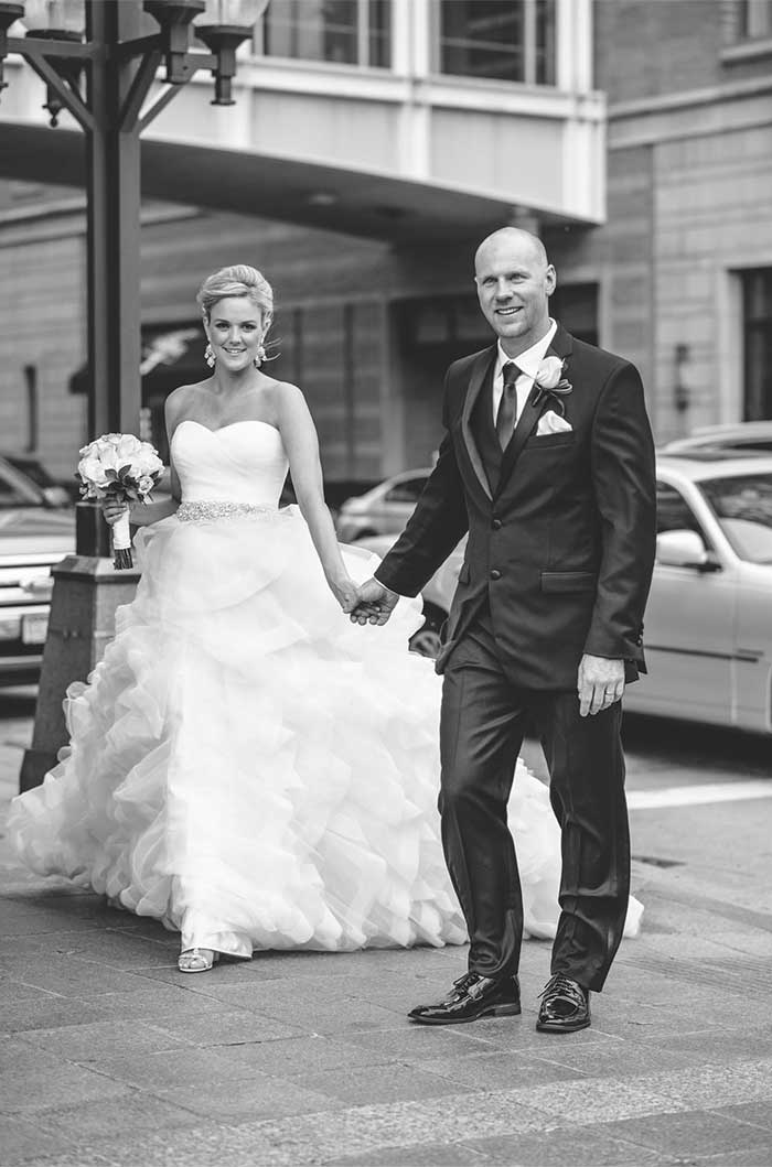 a wedding couple on the sidewalk near a downtown street