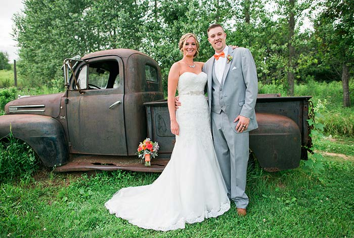 a wedding couple standing in front of a vintage truck