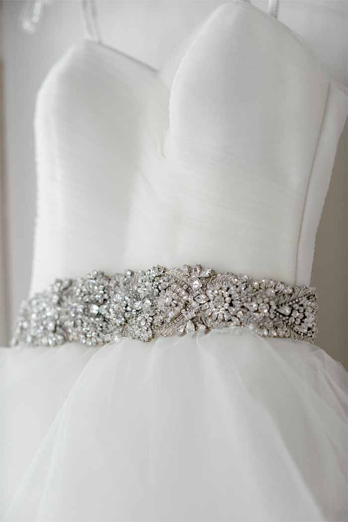 a wedding dress with a crystal belt